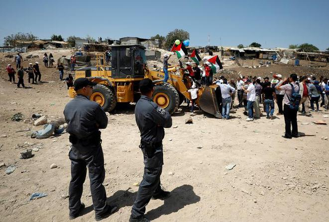 Des Palestiniens bloquent un bulldozer israélien dans le village bédouin de Khan Al-Ahmar, en Cisjordanie occupée. © Reuters