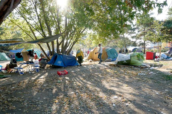 Le soleil inonde cette place et ses arbres. Les tentes sont démontées une à une. © Georges