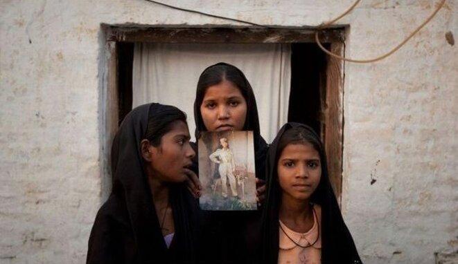 Les filles d'Asia Bibi montrant la photo de leur mère, le 13 novembre 2010. © Reuters