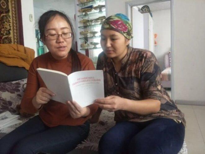 Une employée envoyée par l'Etat, lit le rapport de Xi Jinping du 19e Congrès national du Parti communiste chinois à son «parent» ouïghoure. Cette image a été publiée sur WeChat par la Ligue de la jeunesse communiste du Xinjiang.