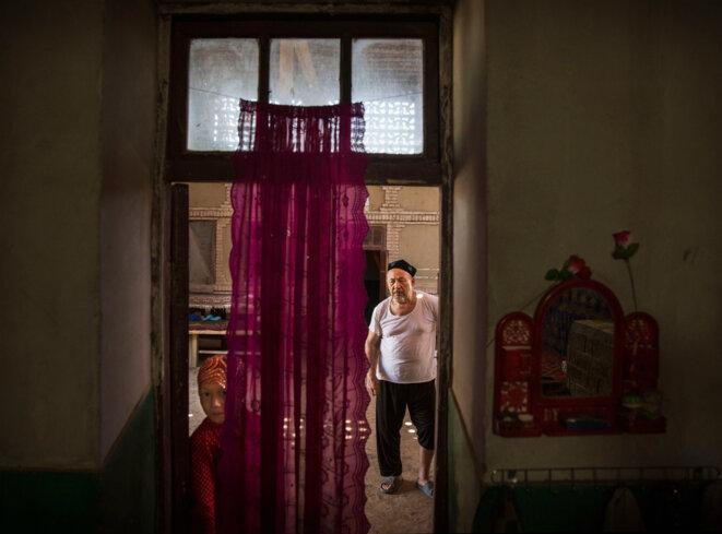 Un homme ouïghour et sa petite-fille chez eux après un repas lors de la fête Qurban à Turpan, dans le Xinjiang, le 12 septembre 2016. © Kevin Frayer/Getty