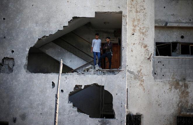 Dos palestinos observan los daños causados por un ataque israelí en su edificio en Gaza, el 12 de noviembre de 2018. © Reuters