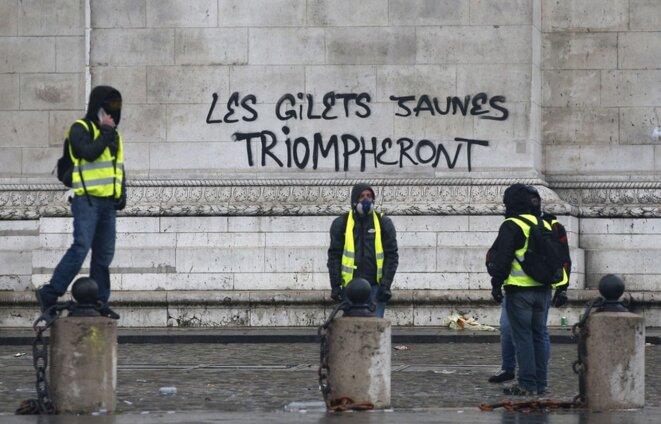 gilets-jaunes-posent-devant-tag-inscrit-arc-triomphe-paris-1er-decembre