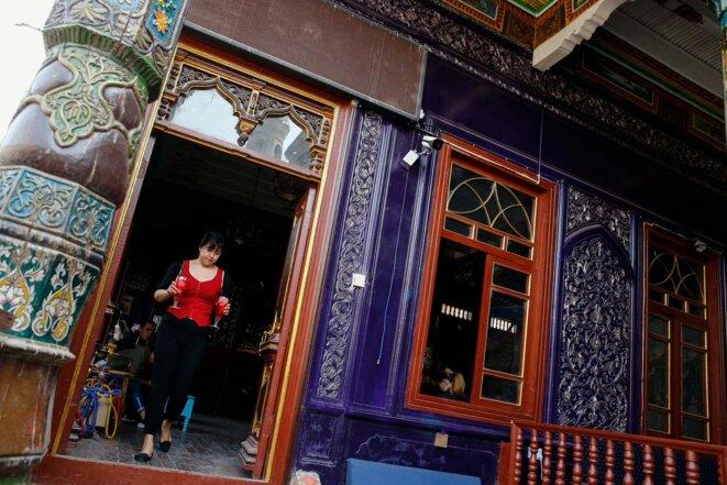 Une serveuse porte des boissons dans un bar situé dans une ancienne mosquée de la vieille ville de Kashgar. © Reuters/Thomas Peter