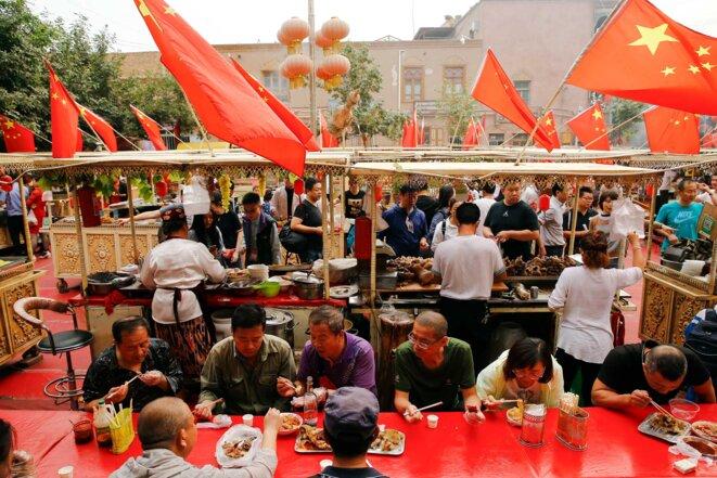 Un marché alimentaire dans la vieille ville de Kashgar est maintenant rempli de touristes chinois Han et orné de drapeaux chinois. © Reuters/Thomas Peter