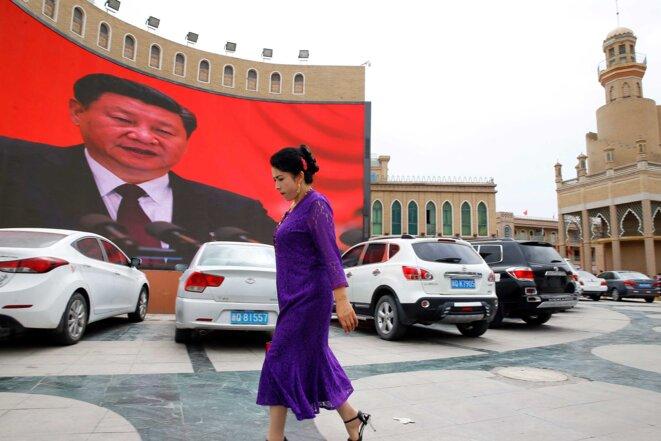 Une femme ouïgoure passe devant un écran géant qui diffuse des messages du Parti communiste et des images du président Xi Jinping sur la place principale de Kashgar. © Reuters/Thomas Peter