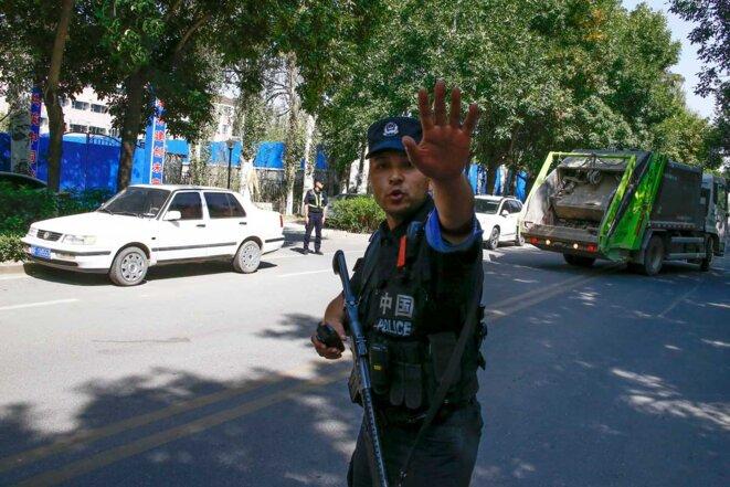 Un officier de police chinois arrête des journalistes à un barrage routier près de ce qui est officiellement appelé un centre de formation professionnelle à Ghulja, une ville du nord-ouest du Xinjiang. © Reuters/Thomas Peter