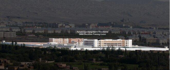 """Les installations de Turpan sont visibles au pied des montagnes de Tianshan, dans le Xinjiang. Un avis d'appel d'offres a révélé que les responsables locaux souhaitaient pouvoir écouter les appels téléphoniques des """"stagiaires"""" au camp. © Reuters/Thomas Peter"""