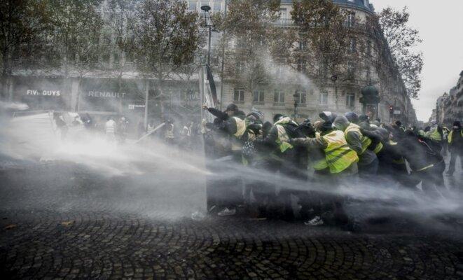 Paris, Champs Elysées le 24 novembre 2018 - Des gilets jaunes se protègent des canons à eau des CRS © SIPA