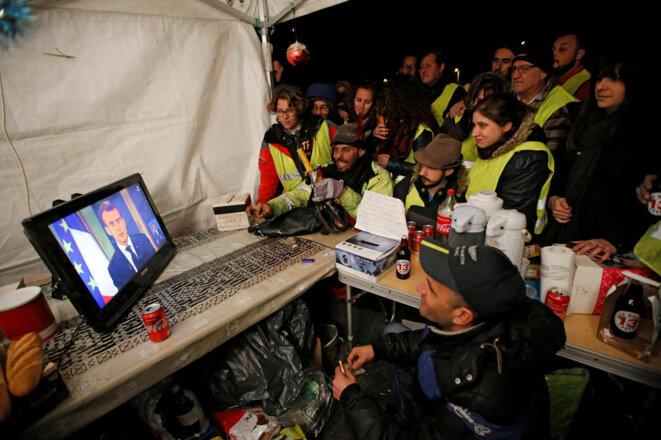 Des « gilets jaunes » de La Ciotat regardent le discours d'Emmanuel Macron, lundi 10 décembre. © Reuters