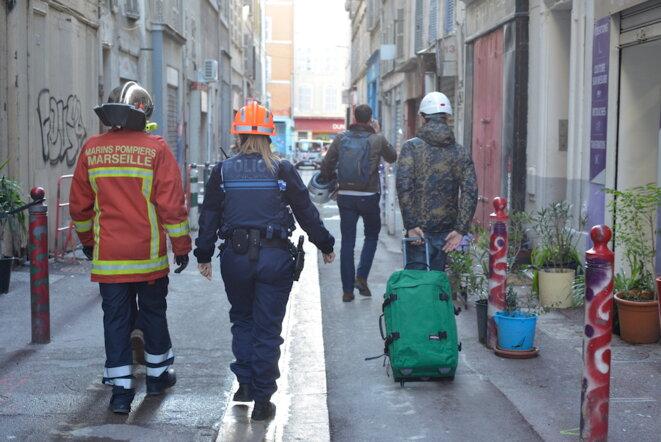 Des marins pompiers escortent des habitants venus chercher des affaires dans les immeubles évacués à Marseille. © LF