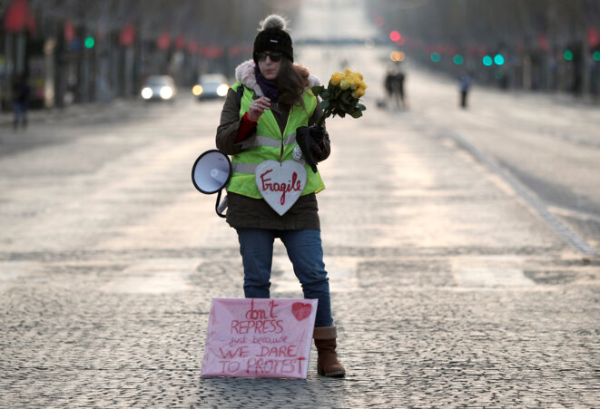 Une manifestante, le 15 décembre 2018, sur l'avenue des Champs-Élysées à Paris. © Reuters