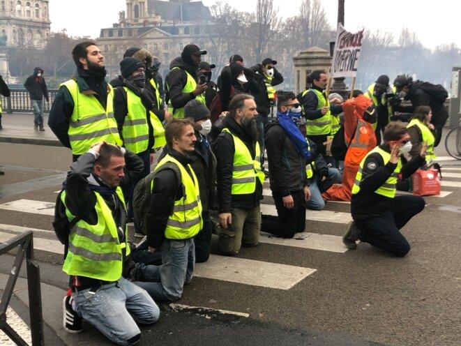 Giles jaunes faisant face à la police, pont d'Arcole, près de l'hôtel de ville de Paris, samedi. © Karl Laske