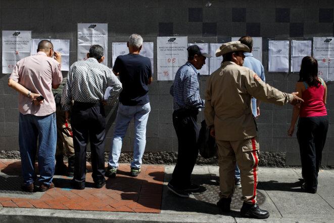 Des Vénézuéliens lisent les listes électorales, le 9 décembre 2018 à Caracas. © Reuters