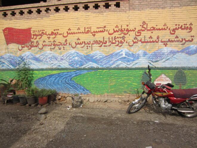 """Un slogan peint sur un mur dans un quartier de Turpan, qui se lit en ouïghour : «Aimer la patrie et le Xinjiang; l'unité - faire des contributions; travailler dur; s'entraider; ouverture; progresser. """" © Elise Anderson"""