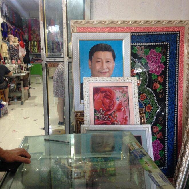 Une photo de Xi Jinping exposée bien en évidence dans un magasin d'un bazar de Qomul © Elise Anderson