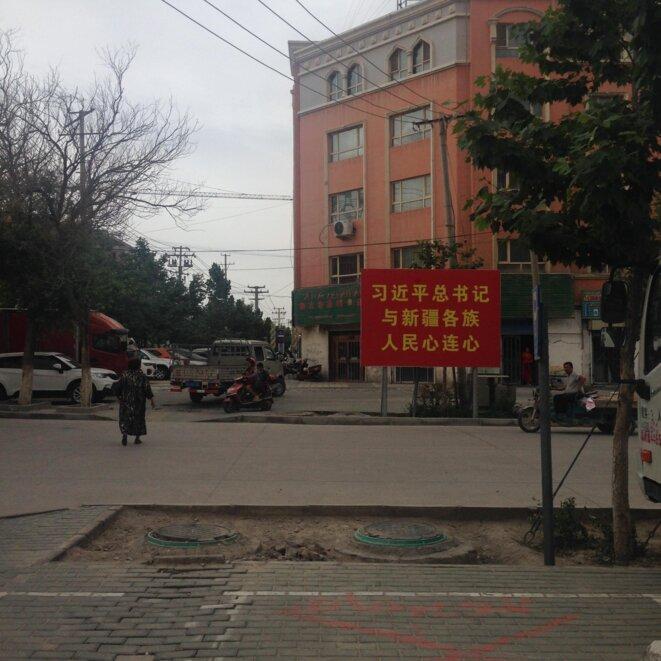 Une pancarte au coin d'une rue assoupie près du site de la mosquée Altun (or) de Yarkend et de l'ancien complexe royal indique: «Le cœur de Xi Jinping et ceux des habitants des différentes ethnies du Xinjiang sont liés». © Elise Anderson
