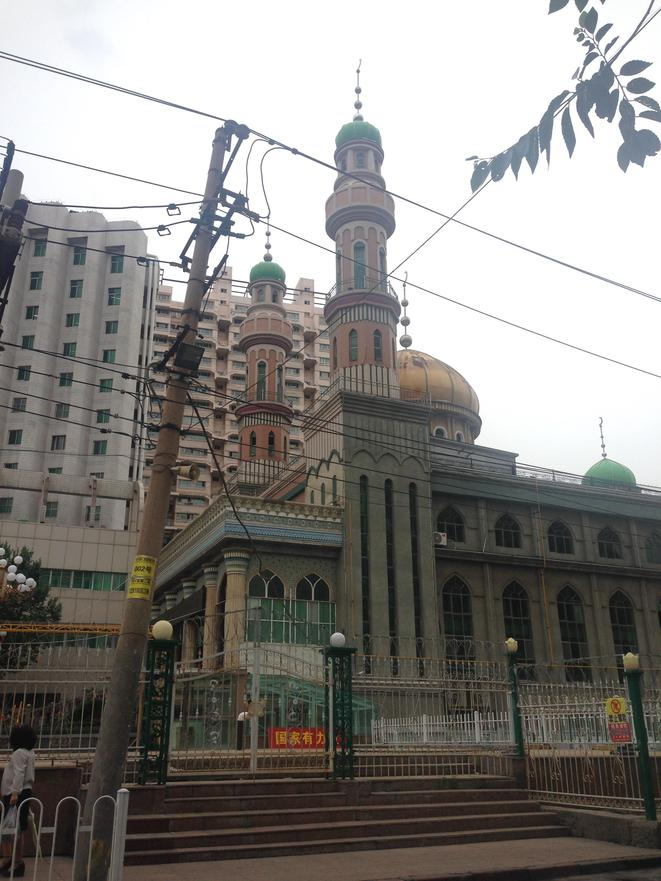 """Vue de la mosquée Noghay (tatare), la plus grande mosquée d'Ürümchi, de Konsul Kochisi (Rue du Consulat, petite rue bordée exclusivement d'entreprises ouïghoures). La mosquée est techniquement """"ouverte"""" comme d'habitude - mais presque personne n'ose y entrer, le complexe étant maintenant bouclé avec des clôtures et des barbelés. © Elise Anderson"""