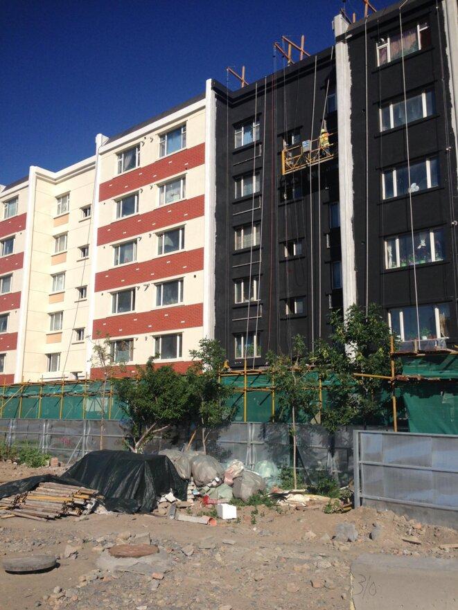 Dans l'ensemble d'Ürümchi, des bâtiments sont en train d'être rénovés dans le but de gentrifier la ville. Une deuxième phase du projet consiste à réinstaller des personnes de différents groupes ethniques dans la ville une fois les travaux de rénovation terminés. © Elise Anderson