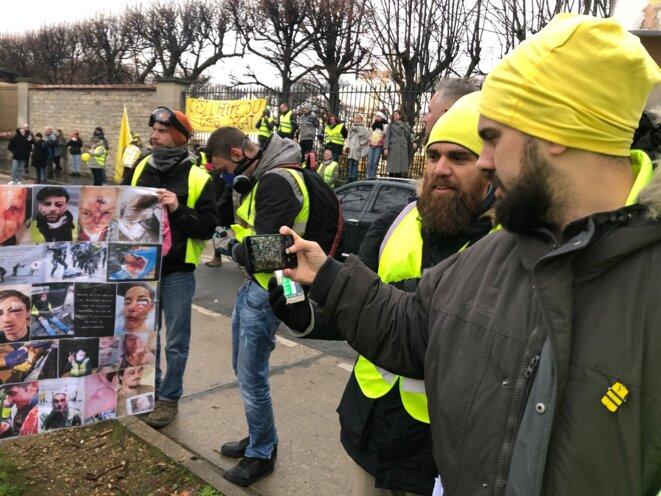 Éric Drouet devant une banderole avec des visages de manifestants mutilés © Karl Laske