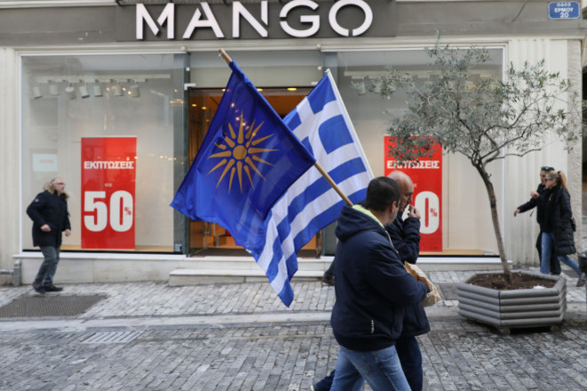 """Le drapeau arborant le soleil à douze branches, mais sur fond bleu, est brandi par des manifestants grecs qui revendiquent """"l'hellénicité exclusive"""" de la Macédoine"""