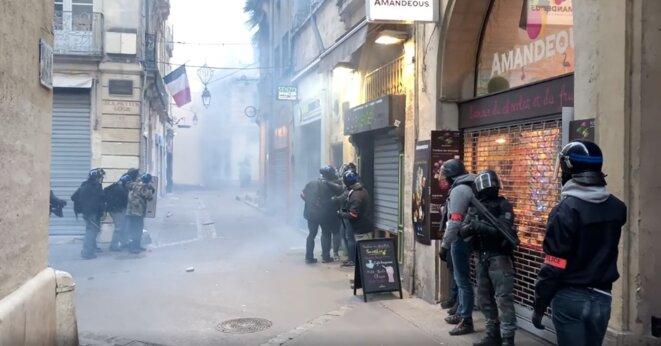Capture d'écran d'une vidéo filmée par un commerçant à Montpellier, le 12 janvier 2019. L'agent de la BRI armé d'un fusil à pompe apparaît en pantalon de treillis à droite. © DR