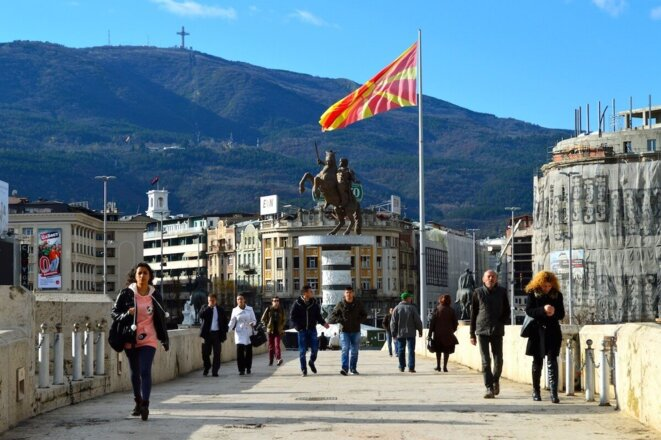 Vue de Skopje avec en arrière plan le drapeau officiel de la MdN et la statue d'Alexandre. L'accord de Prespa prévoit la suppression en MdN de monuments se référant au patrimoine historique de la Grèce.