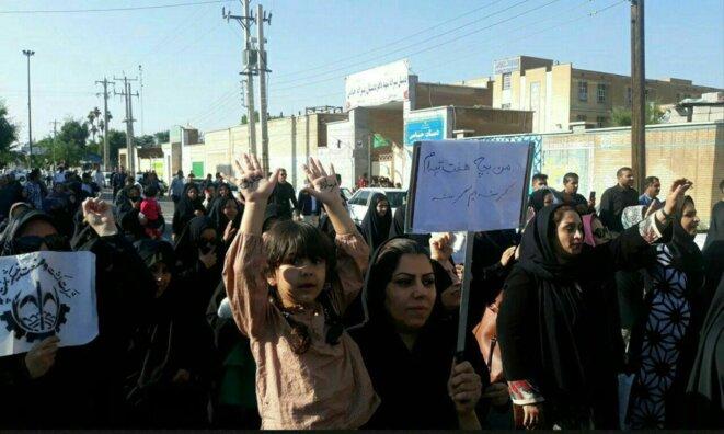 """Manifestation des femmes des ouvriers du sucre en Iran. Sur la pancarte: """"nous sommes les enfants de Haft-Tapeh. Nous avons faim!"""""""