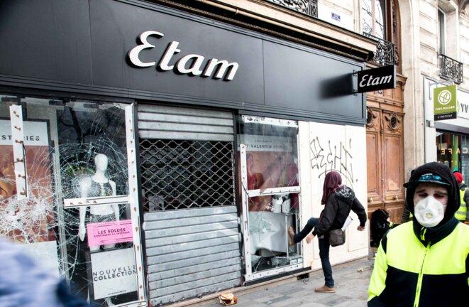 Un casseur brise la vitrine de la boutique Etam place de la république pendant l'acte 12 de la mobilisation des gilets jaunes © Christian DROUET