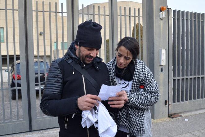 À la sortie du tribunal, Samia lit un mot de son mari, Abdel Zahiri, placé en détention provisoire, aux côtés de Mohamed, son ami d'enfance. © LF