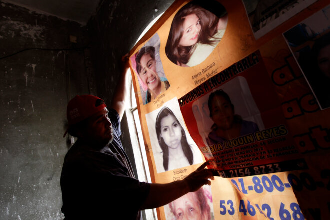 In April 2013 a man displays the photos of women who have died or disappeared in Ecatepec, Mexico. © Henry Romero (Reuters)