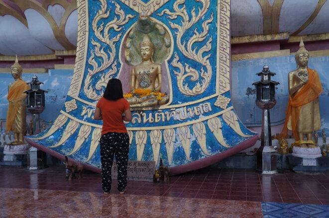 Une femme se recueille à un temple bouddhiste sur l'île de Koh Samui, dans le golfe de Thaïlande. © Laure Siegel