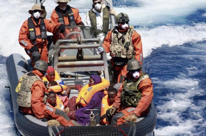 En août 2015, des rescapés sont transférés vers un navire allemand. En violet, une femme enceinte s'apprête à donner naissance à une fillette somalienne, Sophia, qui donnera son nom à l'opération militaire européenne. © Bundeswehr
