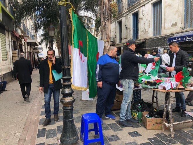 Partout dans la ville, des vendeurs de drapeaux, foulards, écharpes, bracelets, perruques aux couleurs de l'Algérie, emblèmes des manifestants criant le slogan « Un héros, le peuple, c'est notre pays ». © LB