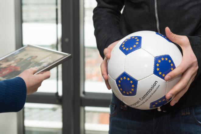 """Les mains de Dimitar Berbatov, à droite, tenant un ballon de football avec l'emblème européen, offert par la DG """"Aide humanitaire et protection civile (ECHO)"""" de la CE © Lieven Creemers - Source: EC - Service audiovisuel. Union européenne, 2015."""