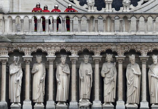 Des pompiers sur la façade de Notre-Dame, au lendemain de l'incendie mardi 16 avril 2019 © Reuters / Yves Herman.