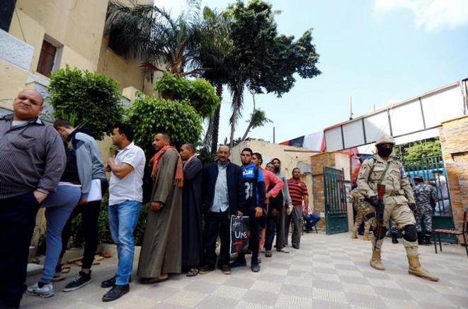 Un soldat monte la garde devant un bureau de vote du Caire, le 21 avril © Reuters