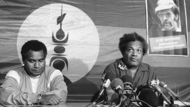 """Tjibaou et Yeiwéné quelques mois avant leur assassinat. A coté du drapeau Kanaky, un poster d'Eloi Machoro """"assassiné par l'ordre colonial francais""""."""