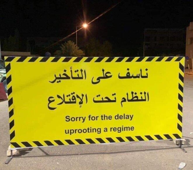 """Un des panneaux, """"désolés pour le temps d'attente, on déracine le régime (littéralement, le régime est sous déracinement, en voie de déracinement"""" / Réseaux sociaux."""