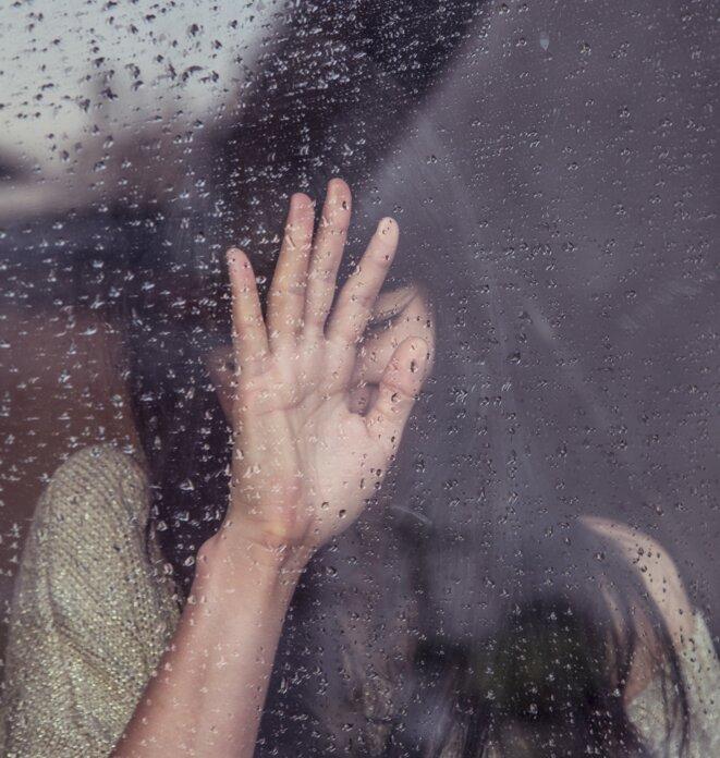 Femme en pleurs devant une vitre © Photo libre de droit