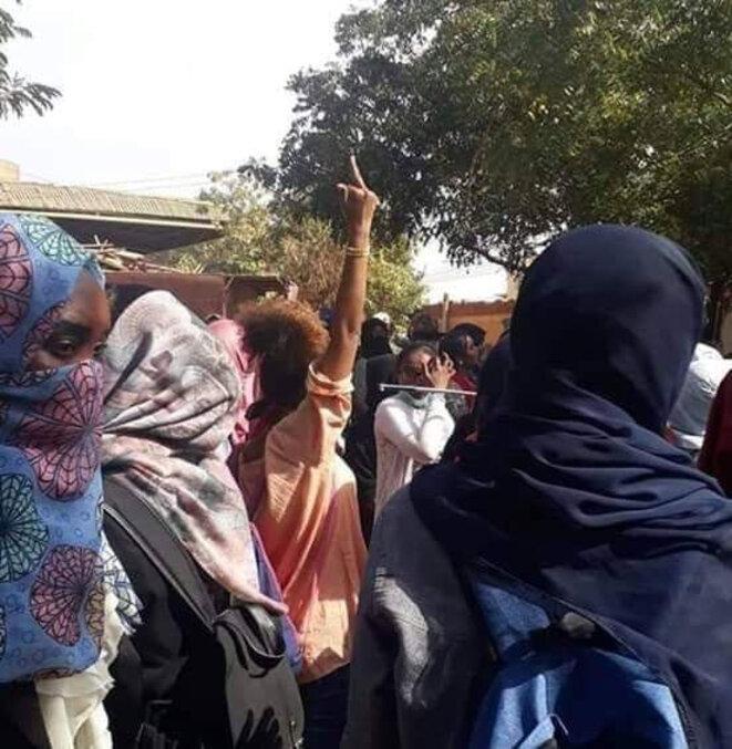 Une manifestante dans un cortège lève un doigt d'honneur au régime. / Réseaux sociaux.