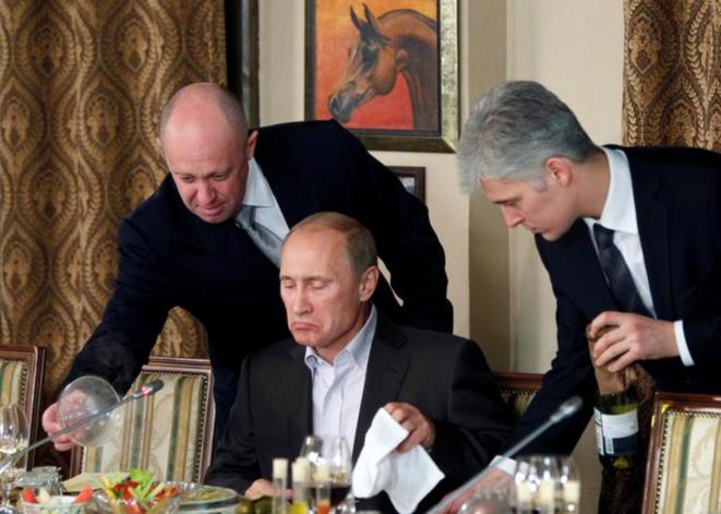 L'oligarque russe Evgeny Prigogine (à gauche) servant Vladimir Poutine. © Reuters