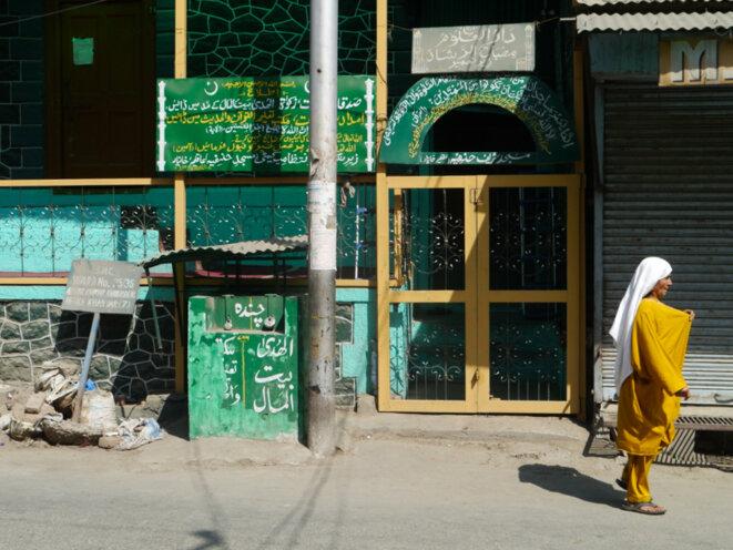 Une femme marche devant une mosquée de la vieille ville à Srinagar © Arnaud Chastagner