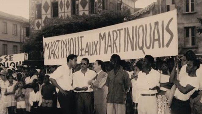 Extrait du film de Camille Mauduech. Au centre sous la banderole, Marc Pulvar et Renaud de Grandmaison