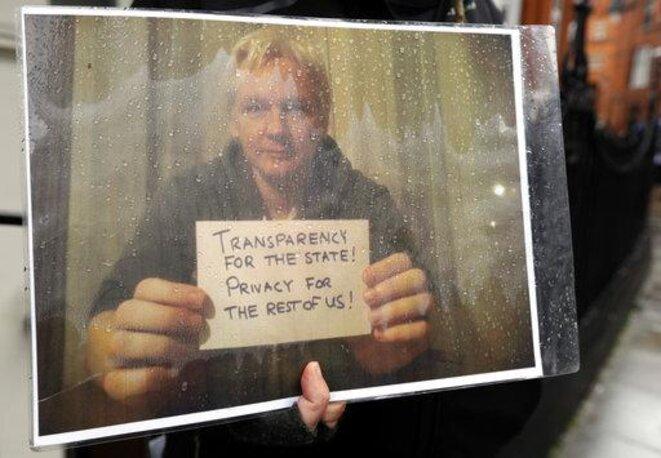Le 29 mars 2018, un manifestant brandit une photo de Julian Assange après que le gouvernement équatorien a coupé les liaisons Internet du porte-parole de Wikileaks toujours enfermé dans une pièce de 20 mètres carrés dans les locaux de l'Ambassade d'Equateur à Londres (AP Photo/Kirsty Wigglesworth)