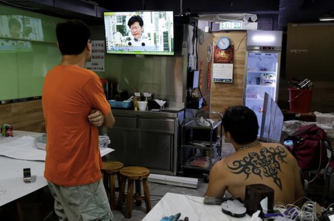 Deux hommes dans un restaurant à Hong Kong regardent l'intervention télévisée de la cheffe de l'exécutif Carrie Lam, annonçant le retrait du texte de loi prévoyant l'extradition vers la Chine, le 15 juin 2019. © REUTERS/Thomas Peter