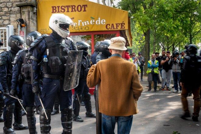 1er mai, des gilets jaunes et des passants observent l'action des forces de l'ordre lors de l'interpellation des manifestants réfugiés dans la cour séparant une résidence du Crous de l'hopital de la pitié salpétrière.