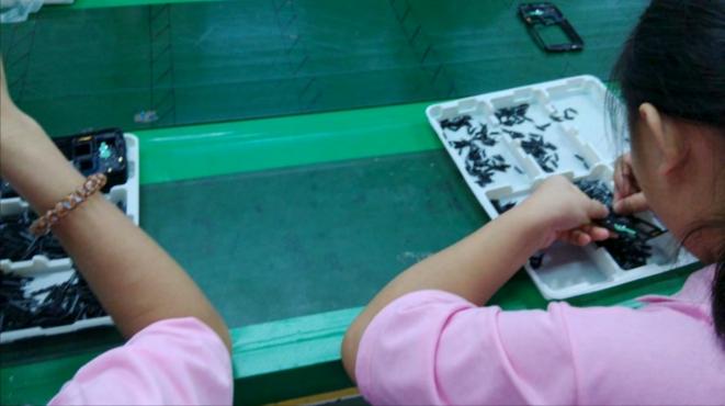 Des enfants assemblent des téléphones portables Samsung. © CLW
