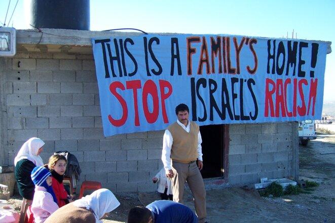 Des habitants palestiniens devant leur maison pour empêcher sa destruction par les forces israëliennes. © ICAHD