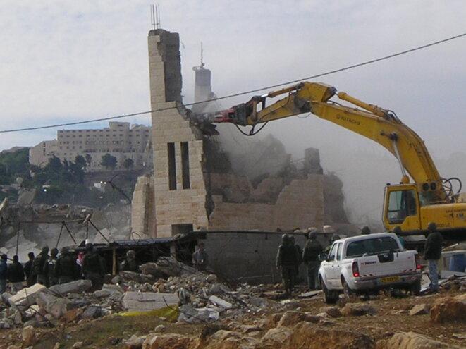 Un bulldozer israélien détruit une habitation palestinienne. © ICAHD